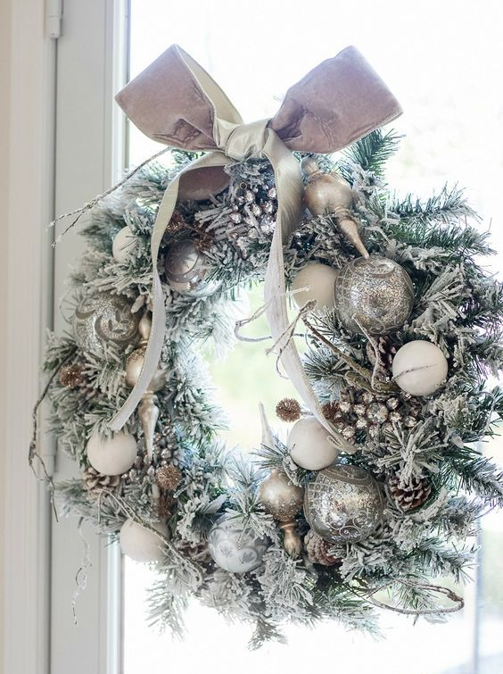 a silver Christmas wreath with snowy pinecones and a bow on top is a chic idea for Christmas decor