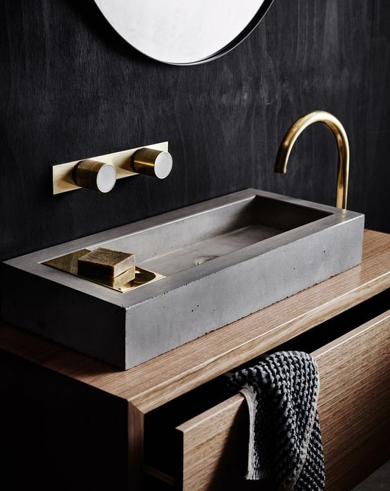 a sleek concrete geometric sink is accented with gold fixtures to give it a softer and chic look