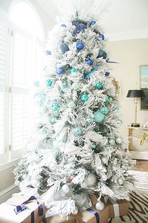 a snowy Christmas tree decorated with ornaments from bright blue to turquoise and silver grey for an ombre effect