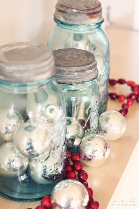 a wooden tray with mason jars filled with silver ornaments and a cranberry garland