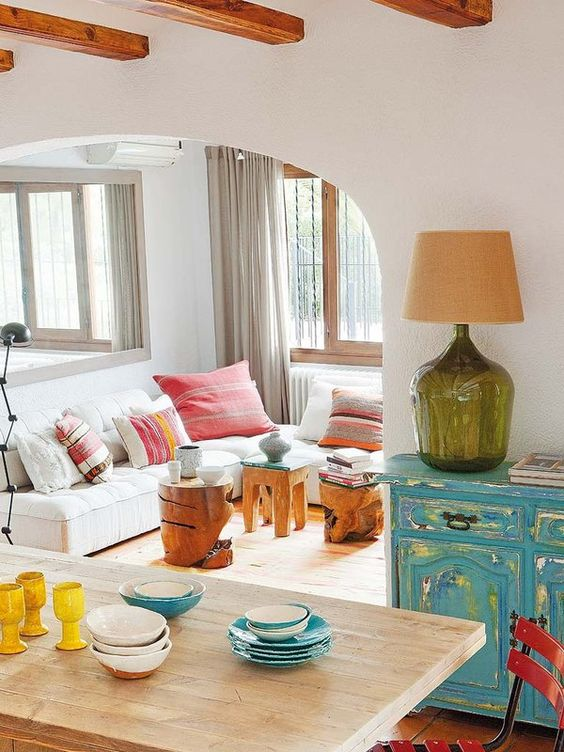 a bright turquoise shabby chic sideboard, some wood carved stools and colorful textiles make up the space