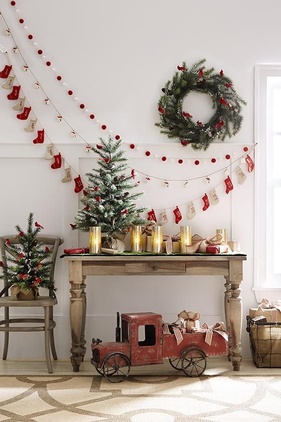 a pompom, paper house and decorative stocking garland plus a wreath on the wall can be a nice idea for a vintage space