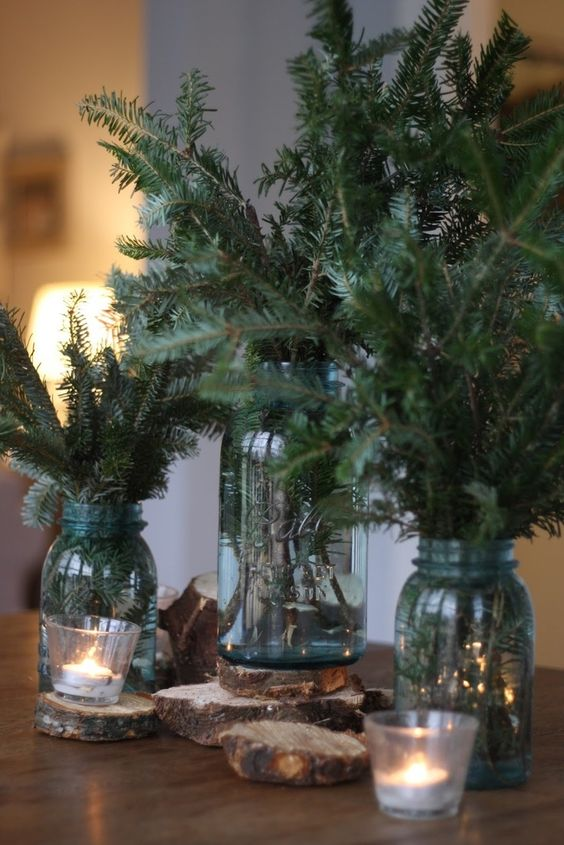 a trio of mason jars with evergreens, candles and wood slices ccan be used as a display or centerpiece
