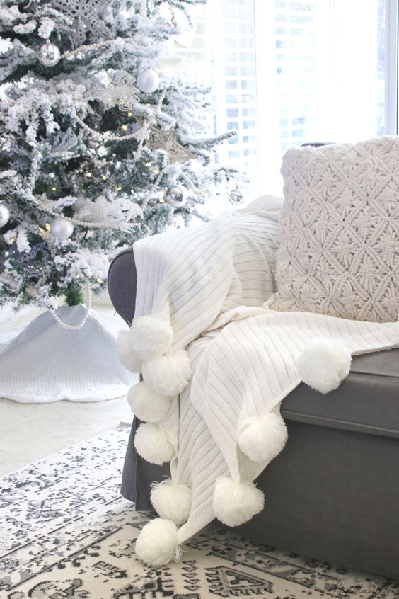 a beautiful white throw with pompoms and a knit pillow is a cool idea for a cozy Christmas nook