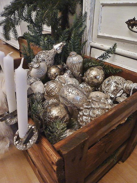 a crate filled with vintage silver ornaments and evergreens is great for any space if your tree can't accommodate them