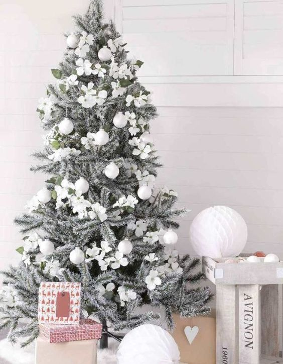 a silver grey Christmas tree with silver and white ornaments is a chic piece that looks frozen