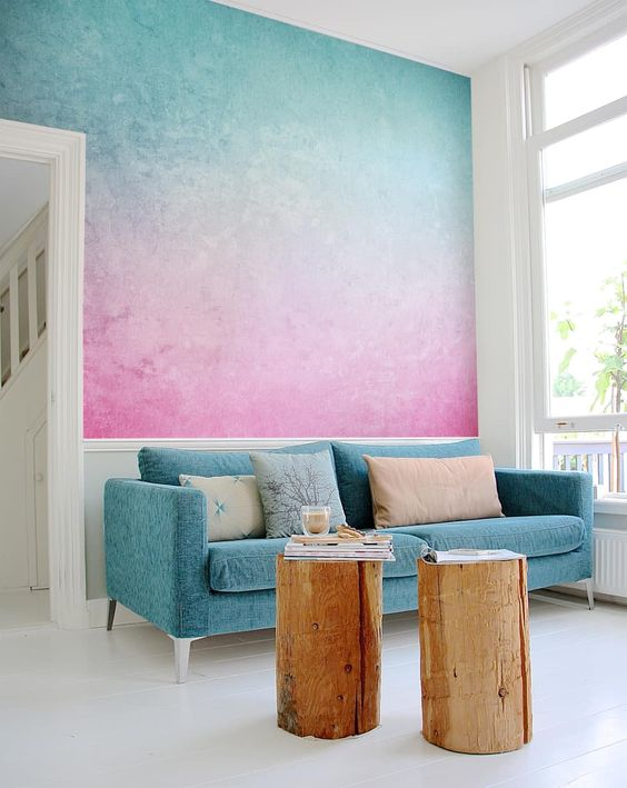 a statement gradient wall in blue and pink plus a matching sofa is a cool idea to impress with bold tones