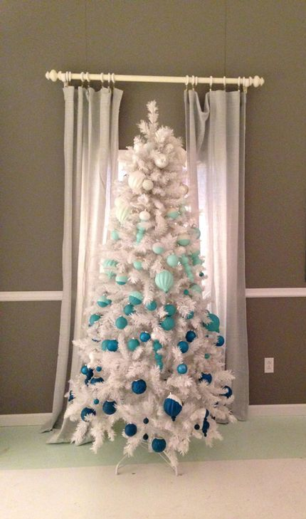 a white Christmas tree with ornaments to achieve an ombre effect from silver to turquoise and navy looks freezing