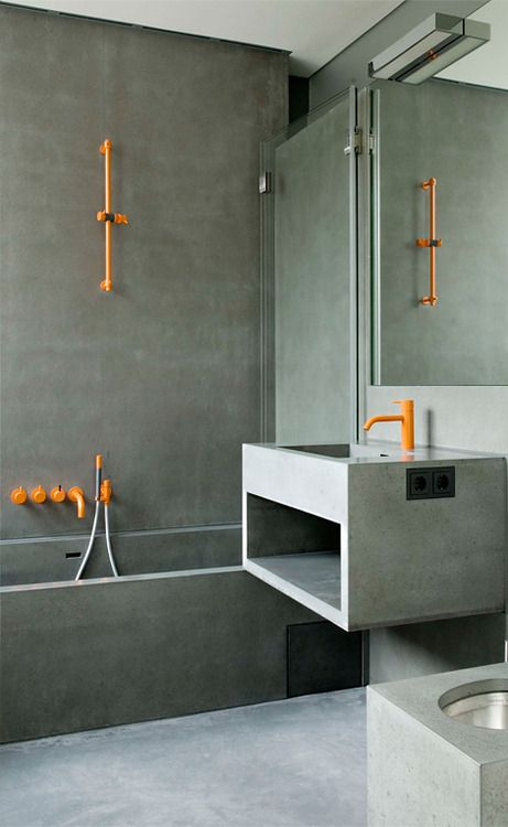 accent your concrete bathroom with bright orange textures to make it more cheerful and vivacious