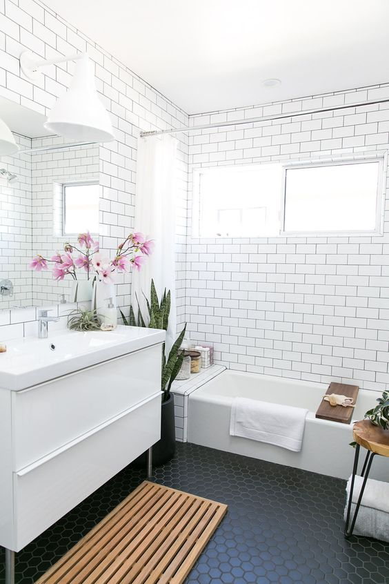 a bathroom clad with subway tiles accented with black grout and black hexagon tiles on the floor is trendy