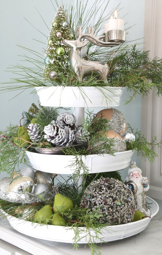 a cupcake stand done in silver and greens, with evergreens, snowy pinecones, deer and Santa figurines and pears
