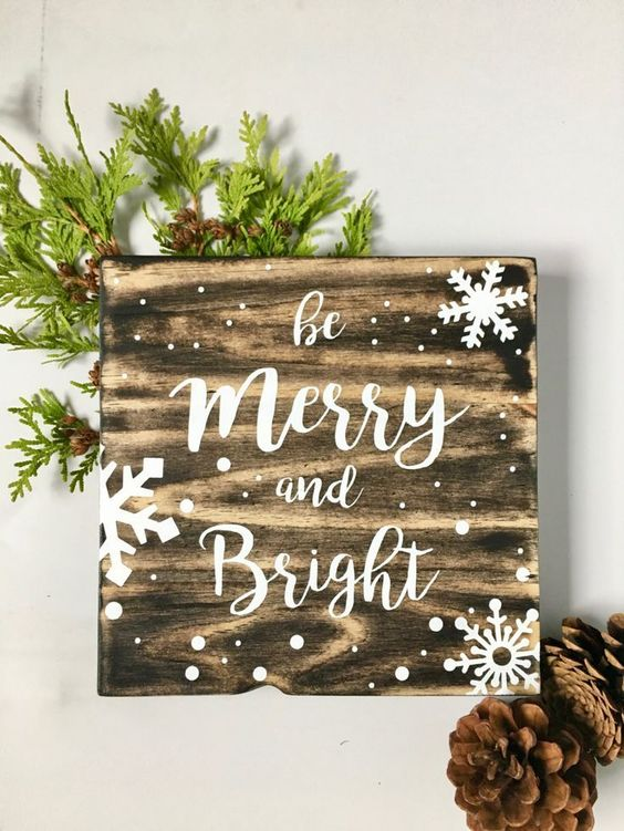a snowy Christmas sign decorated with evergreens is an easy and very cozy holiday craft