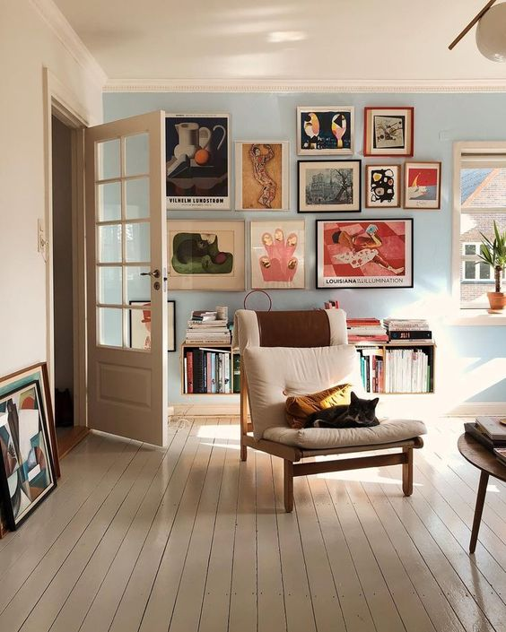an eclectic living room with a gallery wall of colorful artworks that make up the centerpiece of the room