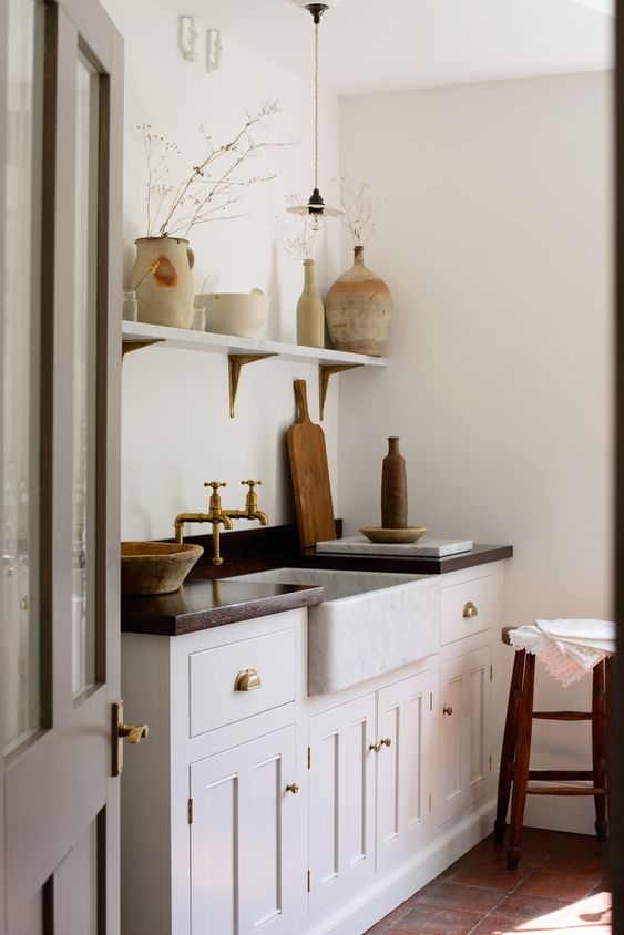 such traditional to vintage cabinets and brass fixtures immediately create a Mediterrranean feel in this Tuscan kitchen