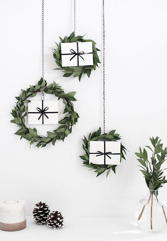a trio of greenery hanging wreaths with gifts for a Scandinavian or minimalist space