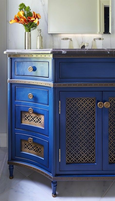 an exquisite Mediterranean vanity in blue with laser cut inserts and vintage knobs brigns Mediterranean chic