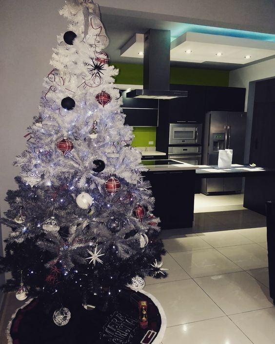 a chic monochromatic ombre white to grey and black Christmas tree with black and white ornaments, copper and snowflake ones