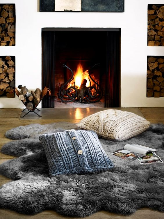 a faux fur rug and cable knit pillows are amazing to create a little cozy nook by the fireplace