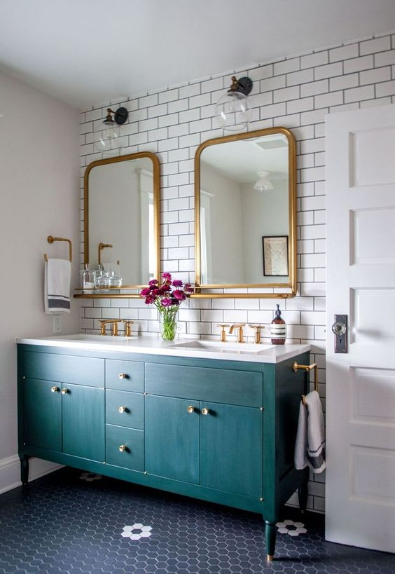 a modern and bold bathroom done with subway tiles with black grout and a bright emerald vanity