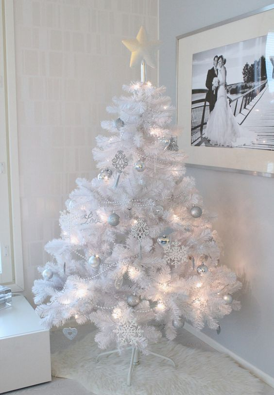 a pure white Christmas tree with lights and silver and white ornaments plus a star on top