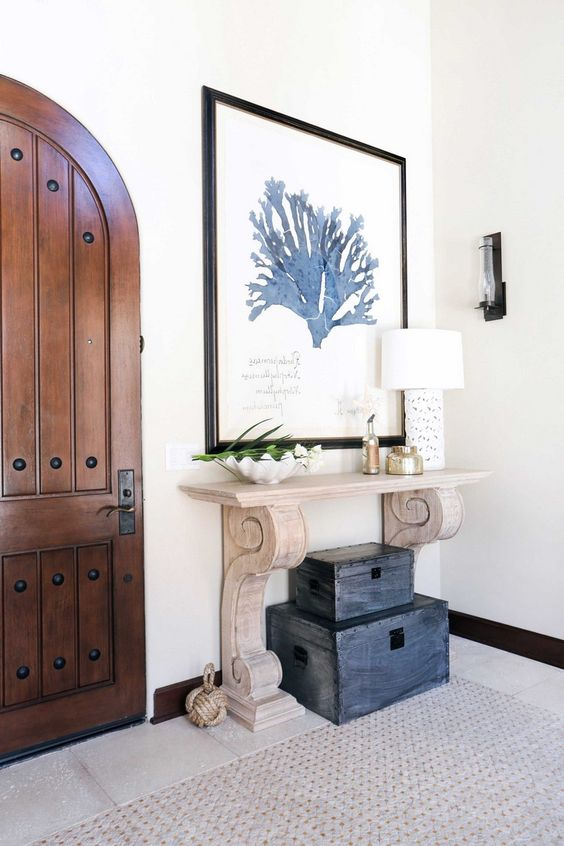 a wood carved console and a stack of vintage chests make the entryway really beachy and Mediterranean