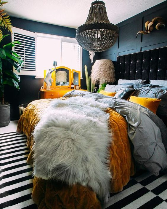 a colorful bed is a statement in this dark and moody bedroom, bright bedding helps with that