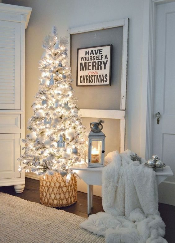 a neutral space is accented with a white Christmas tree with lights, ornaments and faux fur for a charming feel