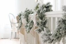 19 a snowy evergreen garland with bows is a great decoration for any space, it's veyr easy to DIY