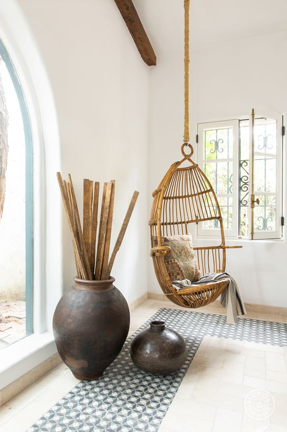 a suspended wicker chair hanging inside will make it feel outside and some dark ceramics and mosaic tiles help creating an ambience
