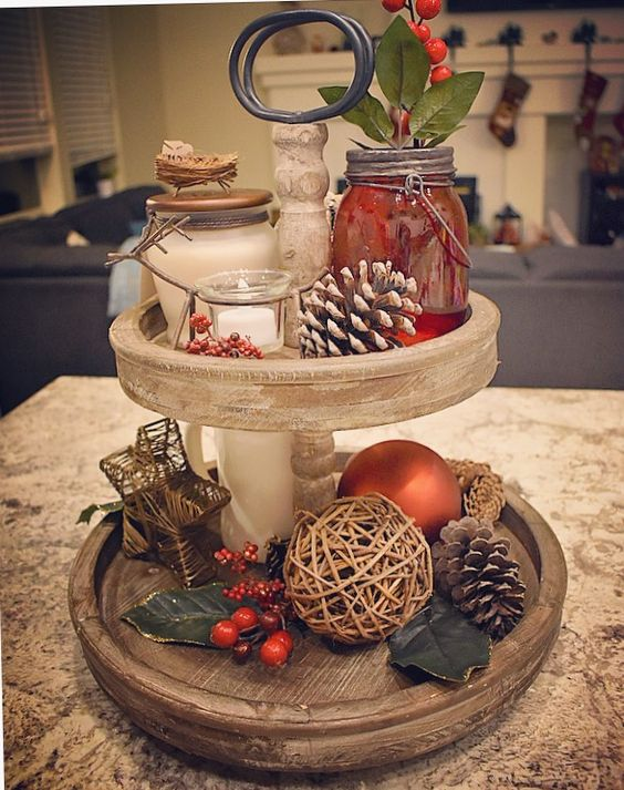 a two-tiered Christmas tray with fake berries, pinecones, a twine ball and beautiful candles