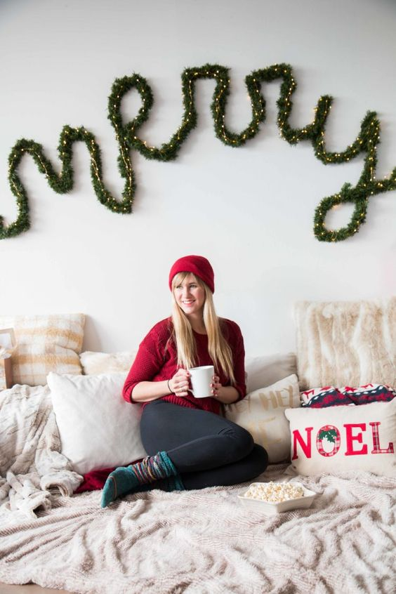 an evergreen and lights letter Christmas garland attached to the wall for a holiday mood