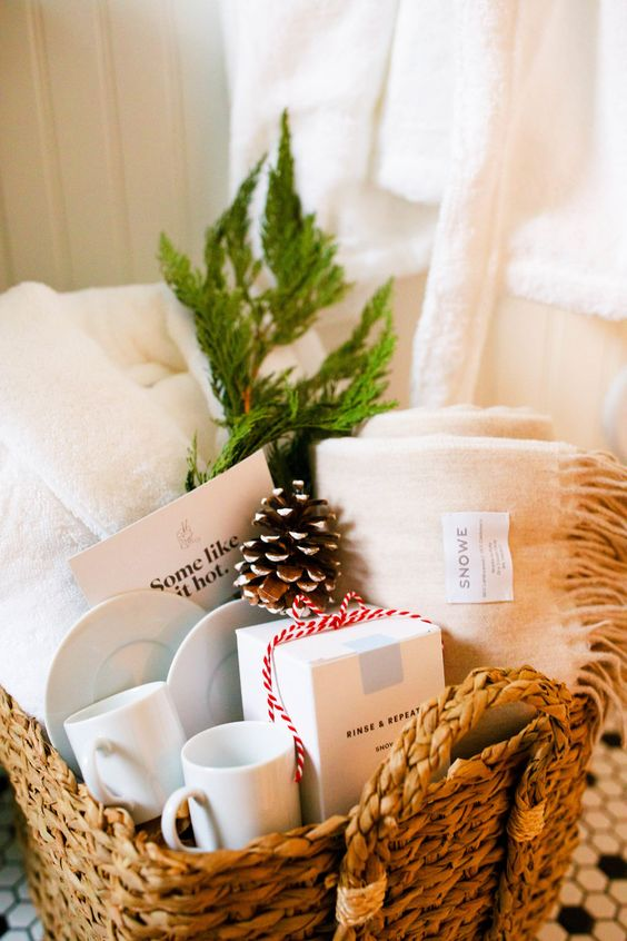 a basket with towels, a snowy pinecones, mugs and evergreens is ideal to take a luxurious bath at Christmas