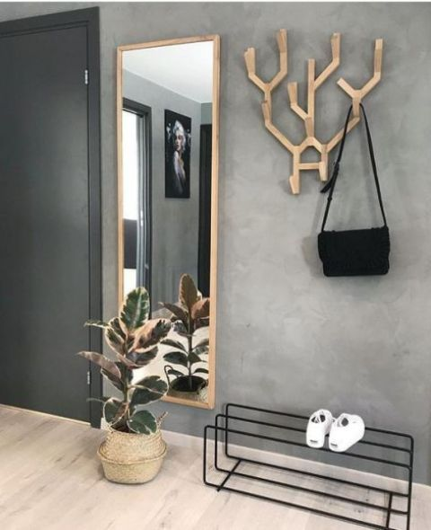a creative wooden antler coat rack and a mirror in a wooden frame make an accent in a minimalist entryway