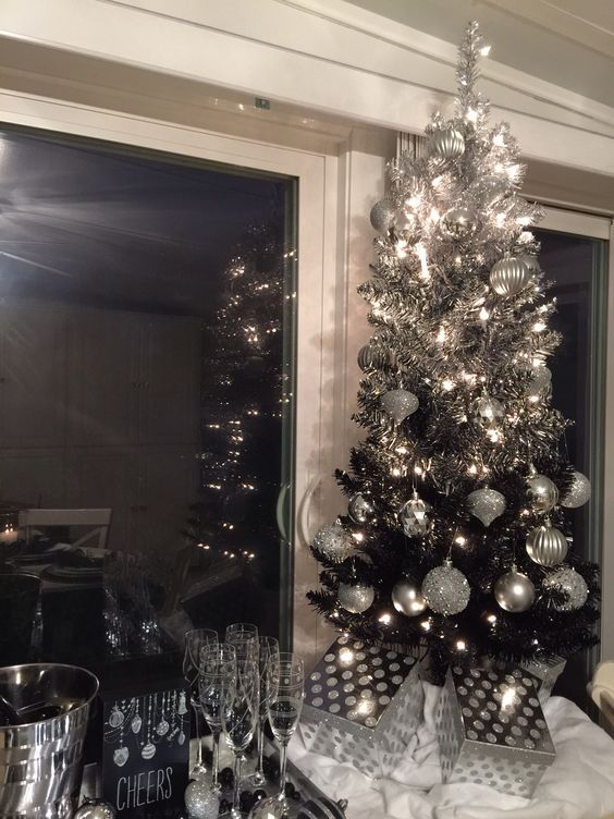 a cute tabletop ombre silver to black tree is styled with glitter and shiny silver ornaments and lights
