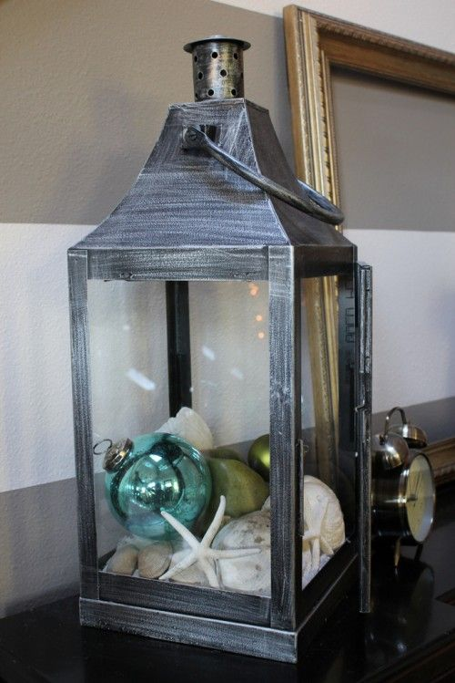a lantern with ornaments, star fish, seashells and sand is a great beachy and coastal display for Christmas