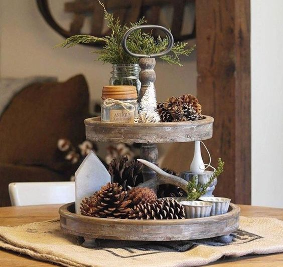a two-tiered tray with pineccones, evergreens, candles and antlers for a woodland or natural feel