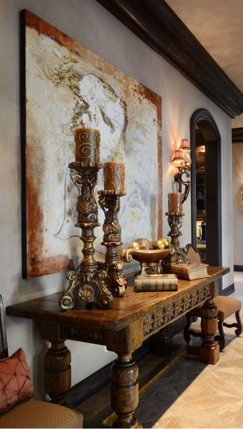 a vintage wooden table and exquisite large candle holders give this space an exquisite Mediterranean feel