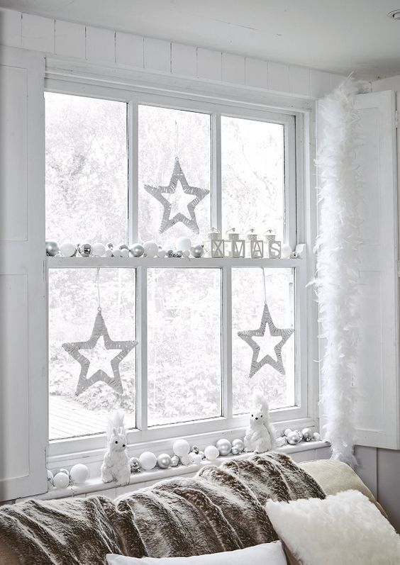 a window decorated in white and silver to create a winter wonderland feel in your space