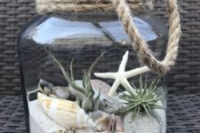 21 a large jar with a beach scene with sand, rocks, driftwood, air plants and seashells plus rope