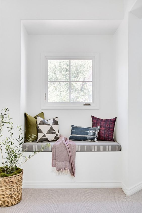 a white space with colorful textiles with prints that make this windowsill bench brighter and catchier