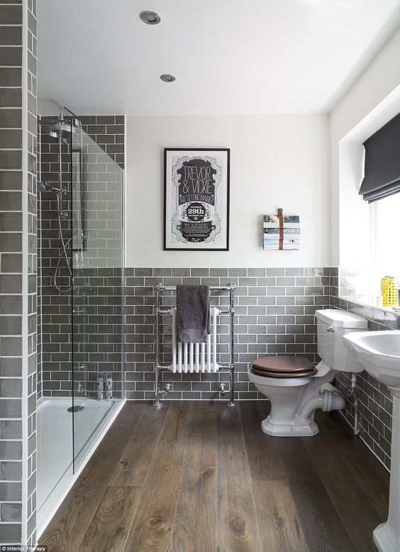 an elegant bathroom clad with grey subway tiles and with wooden floors is a super chic idea