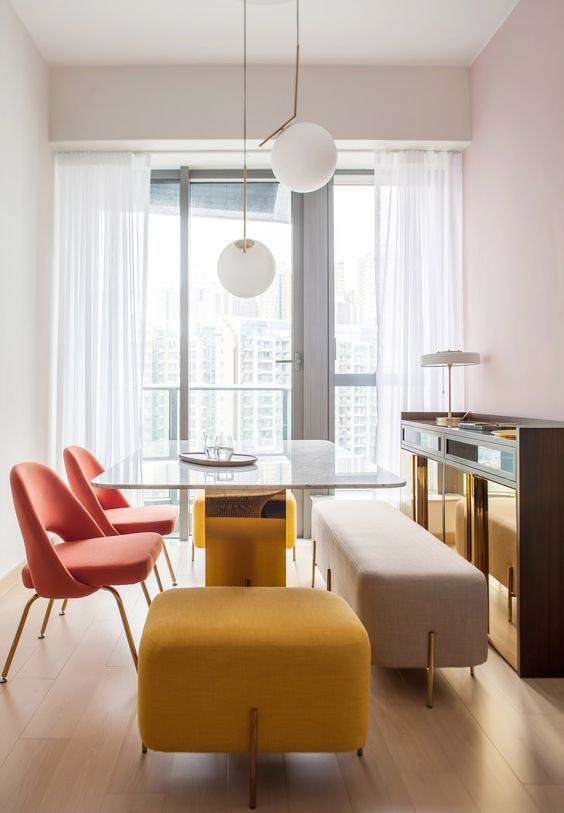 a duo of coral chairs, a yellow upholstered stool and a neutral upholstered bench make the space catchy