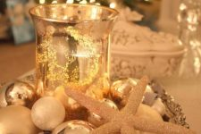 22 a refined display with a vintage tray, metallic ornaments, a glitter star fish and a gold leaf lantern