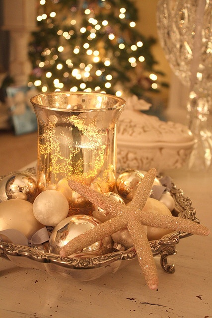 a refined display with a vintage tray, metallic ornaments, a glitter star fish and a gold leaf lantern