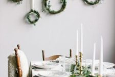 22 a set of greenery wreaths hanging on the wall on a branch is a very chic and natural idea