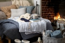 22 a super cozy nook with a large lounger with fabric and knit pillows, knit blankets and fabric throws