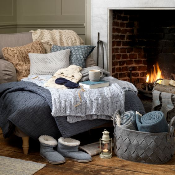 a super cozy nook with a large lounger with fabric and knit pillows, knit blankets and fabric throws