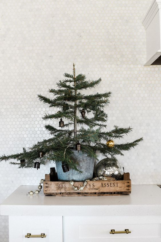 a tray with a large tree in a galvanized bucket, vintage ornaments and an oversized one
