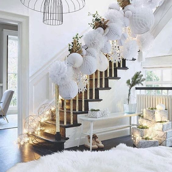 a white hallway with a faux fur rug, white paper ornaments attached to the railing and lots of light lining up the stairs