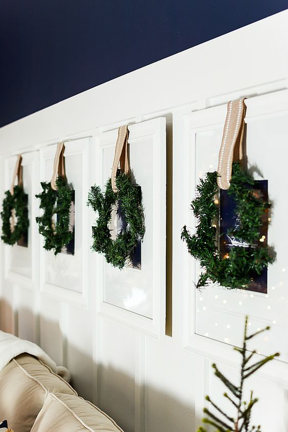 family photos hanging on the wall are covered with greenery wreaths and ribbons for a festive feel